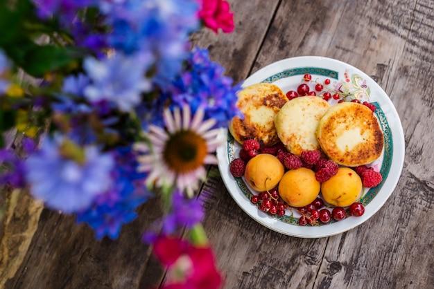 Martwa natura z kwiatów i pieczenia z jagodami na drewnianym stole.
