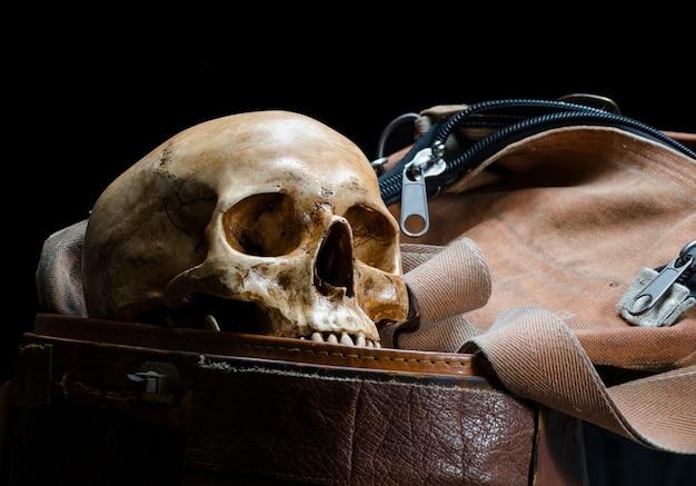 Martwa natura z ludzką czaszką jest umieszczona w starym skórzanym pudełku na czarnym tle