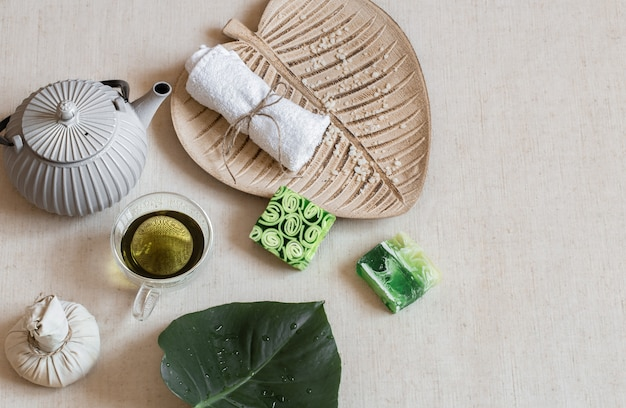 Martwa natura z mydłem, ręcznikiem, liśćmi i zieloną herbatą. pojęcie zdrowia i urody.
