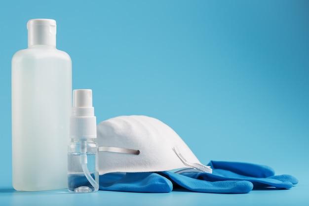 Martwa natura z ochroną antywirusową na niebieskim tle, maska, gumowe rękawiczki, butelka dezynfekcji rąk, żel antyseptyczny.