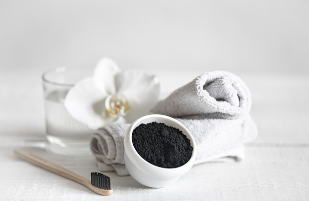 Martwa natura z organiczną drewnianą szczoteczką do zębów ze szklanką wody i naturalnym proszkiem do wybielania zębów. higiena jamy ustnej i pielęgnacja zębów.