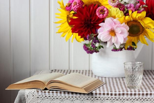 Martwa natura z otwartą książką i bukietem na stole.