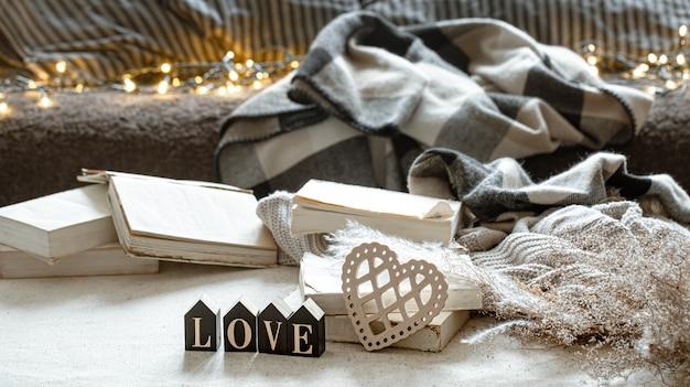 Martwa natura z ozdobnym słowem miłość, książkami i przytulnymi rzeczami.