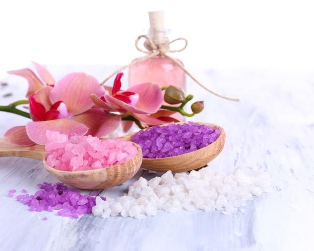 Martwa natura z pięknym kwitnącym kwiatem orchidei i drewnianymi łyżkami z solą morską na drewnianym stole