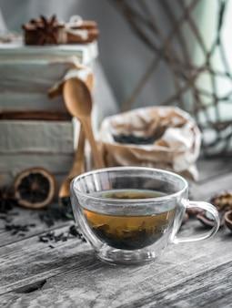 Martwa natura z przezroczystą filiżankę herbaty na drewnianym tle