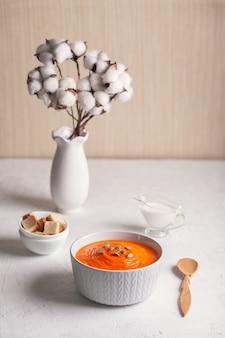 Martwa natura z puree z zupy dyniowej z bułką tartą, śmietaną i nasionami na białym tle. skopiuj miejsce.
