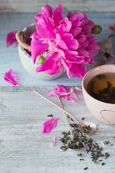 Martwa natura z różowymi kwiatami piwonii i filiżanką ziołowej lub zielonej herbaty na rustykalnym drewnianym tle