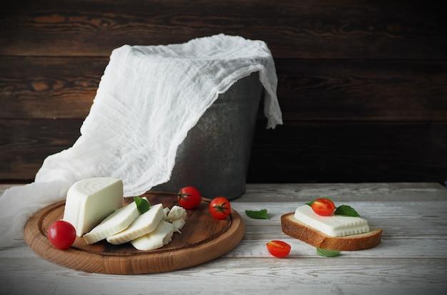 Martwa natura z serem, pomidorami i ziołami na rustykalnym stole. koncepcja zdrowej żywności.