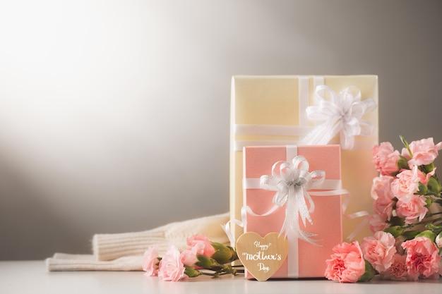 Martwa natura z słodkie kwiaty goździka i prezent na stole, koncepcja dzień matki