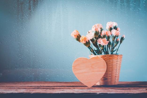 Martwa natura z słodkimi kwiatami goździka w koszu na drewnianym stole, serce drewniane puste na szczęśliwy dzień matki i koncepcja walentynki