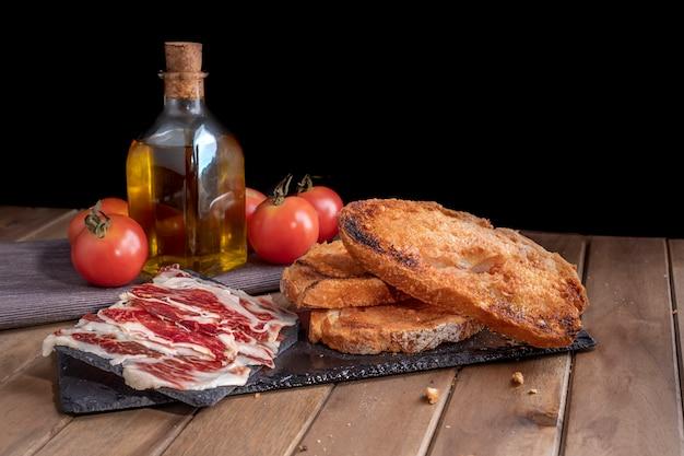 Martwa natura z szynki iberyjskiej z pomidorowym chlebem, czerwonym winem i dodatkową oliwą z oliwek na tacce z łupków. czarne tło.