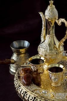 Martwa natura z tradycyjnym złotym arabskim zestawem kawy z dallah, dzbankiem do kawy i datami.