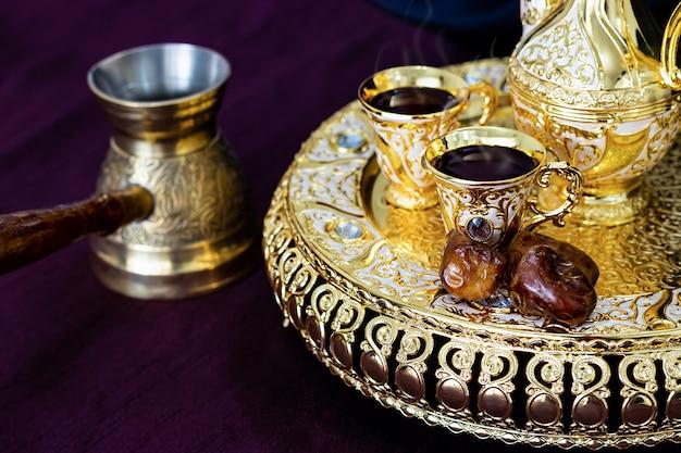 Martwa natura z tradycyjnym złotym arabskim zestawem kawy z dallah