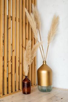 Martwa natura z trawy pampasowej w szklanych butelkach na drewnianej podłodze. wystrój wnętrz domu. suche kwiaty w wazonach na tle drewnianej ściany w studio