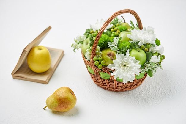 Martwa natura z wiklinowym koszykiem wypełnionym owocami, białymi kwiatami i otwartą książką