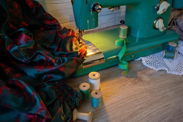 Martwa natura z zabytkową elektryczną maszyną do szycia, tkaninami i szpulami nici
