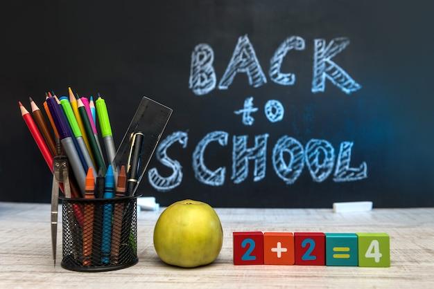 """Martwa natura z zegarem, materiałami do pisania, książką i jabłkiem na tle tablicy z napisem """"powrót do szkoły""""."""