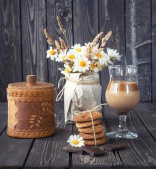 Martwa natura z zimną kawą z mlekiem i czekoladą z ciasteczkami owsianymi i bukietem pięknych stokrotek w stylu rustykalnym na drewnianym tle