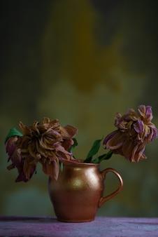 Martwa natura z zwiędłych kwiatów w miedzianym wazonie, na drewnianym stole, na abstrakcyjnym, ciepłym tle teksturowanej ściany.