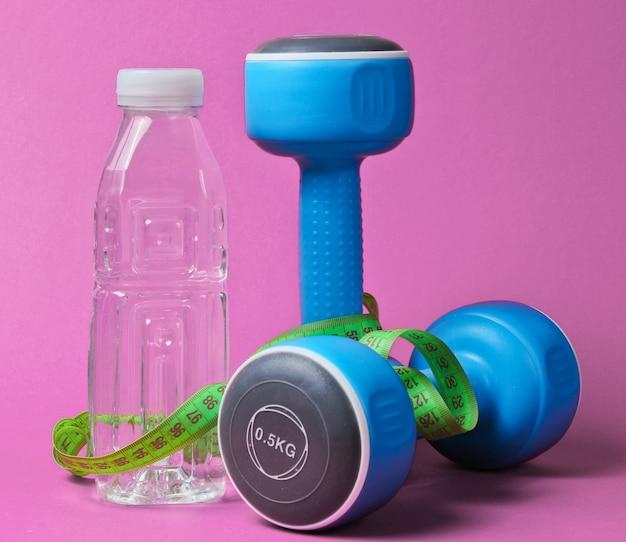 Martwa natura zdrowego stylu życia. hantle, linijka, butelka wody na różowo.