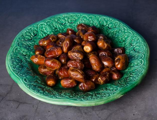 Martwa natura ze słodkimi suszonymi owocami palmy daktylowej na vintage piala, ramadan, ramadan, tradycyjne jedzenie.