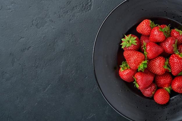 Martwa natura ze świeżą truskawką w czarnej misce. widok z góry zdjęcie soczystych truskawek. koncepcja zdrowego odżywiania. widok z góry z miejsca na kopię.