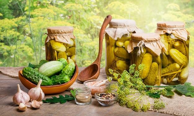 Martwa natura ze świeżymi i konserwowymi ogórkami w słoikach, przyprawy na drewnianym stole z promieniami słonecznymi zamazanymi przez naturalne tło. warzywa konserwowe