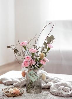 Martwa natura ze świeżymi kwiatami w wazonie i szczegółami świątecznego wystroju wielkanocnego na rozmytym tle