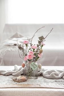 Martwa natura ze świeżymi kwiatami w wazonie i szczegółami świątecznego wystroju wielkanocnego