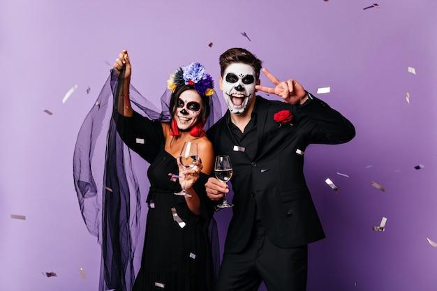 Martwa para pije szampana na halloween. urocza panna młoda zombie, która bawi się na imprezie z chłopakiem.