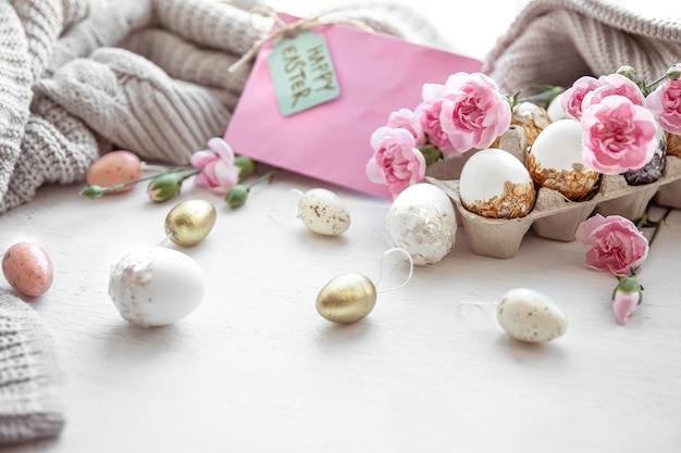Martwa wielkanoc z pisankami, świeżymi kwiatami i elementami dekoracyjnymi z bliska.