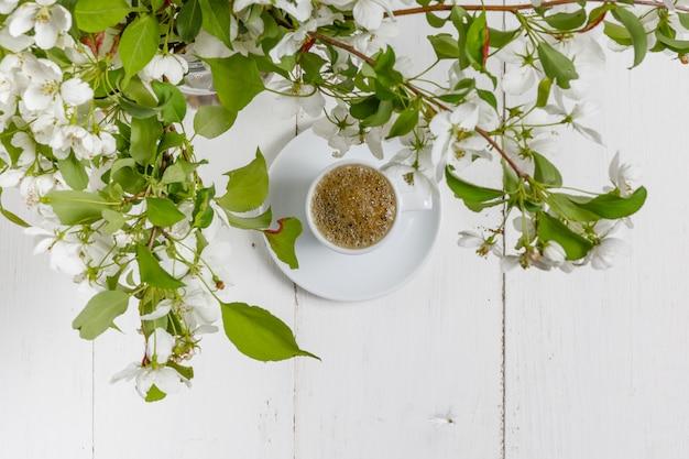 Martwa wiosna filiżanka kawy z kwiatami jabłoni i płatki kwiatów są na białym stoliku kawiarnianym na zewnątrz w kwitnącym ogrodzie