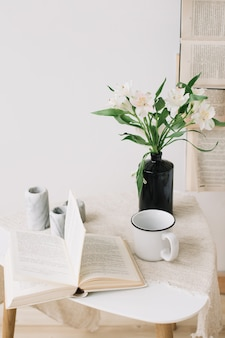 Martwa wiosna. śniadanie w łóżku. biała sypialnia. słodki dom. książki, kwiaty i filiżanka kawy. leżał płasko