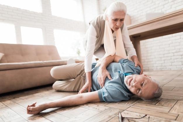 Martwi się dojrzała kobieta pomaga człowiekowi, który ma atak serca.