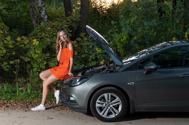 Martwi się kobieta rozmawia przez telefon w pobliżu uszkodzonego samochodu