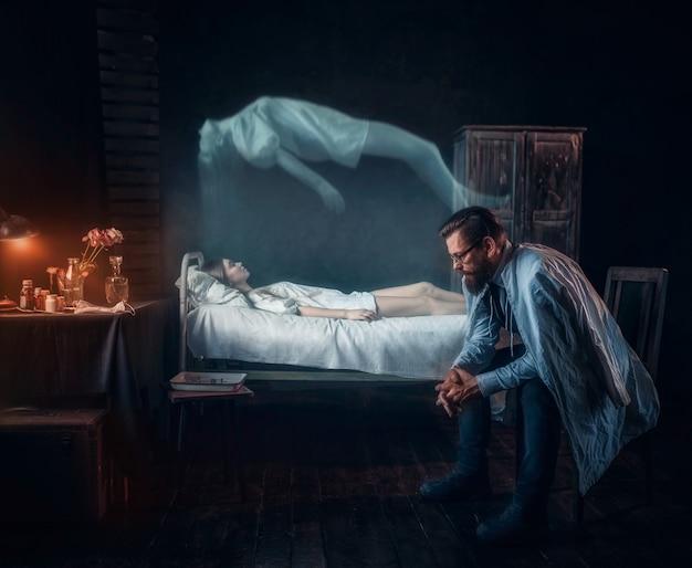 Martwi się mężczyzna przed martwą kobietą, dusza opuściła ciało