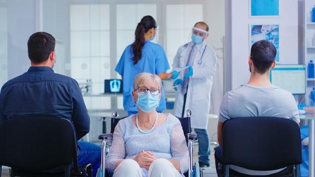 Martwi się niepełnosprawna starsza kobieta siedzi na wózku inwalidzkim w szpitalu poczekalni na badanie lekarskie. stara kobieta nosi maskę przeciw zakażeniu koronawirusem.