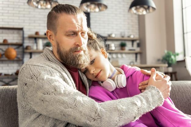 Martwi się o córkę. brodaty ojciec martwił się, że jego nastoletnia córka czuje się przygnębiona