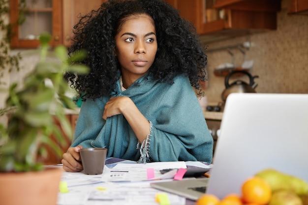 Martwi się piękna african-american kobieta pije kawę przy kuchennym stole