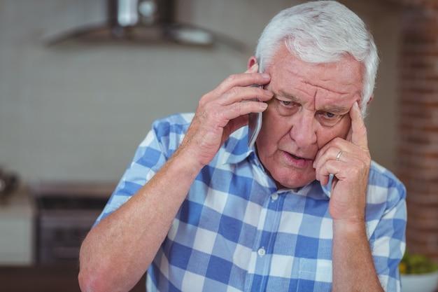 Martwi się starszy mężczyzna rozmawia przez telefon komórkowy