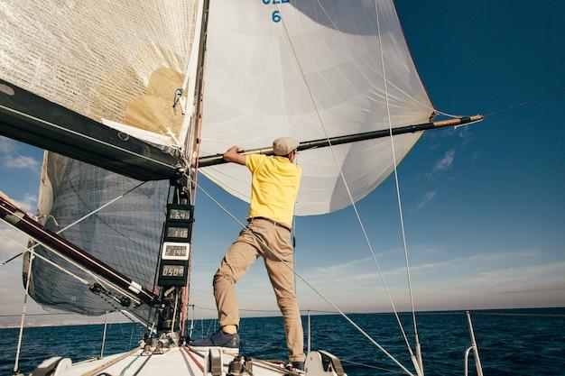 Marynarz obsługuje prywatny jacht w marinie