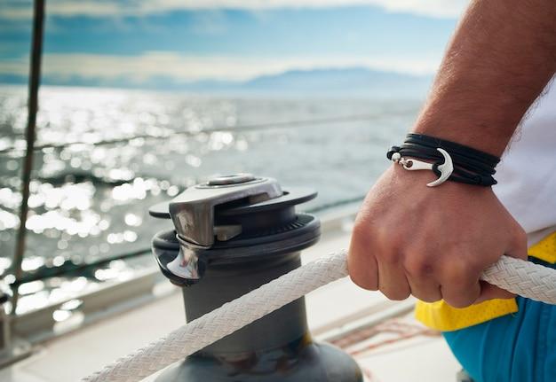Marynarz ręcznie zawijający pelerynę majora, z żeglarską bransoletką