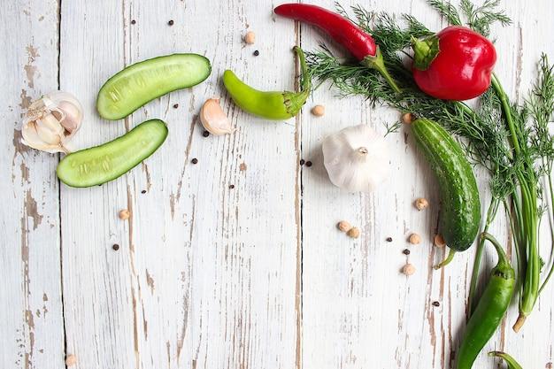 Marynaty na biały drewniany stół z zieloną i czerwoną i papryką chili, kopru włoskiego, soli, czarnego pieprzu, czosnku, grochu, z bliska, zdrowe pojęcie, widok z góry, płaskie świeckich