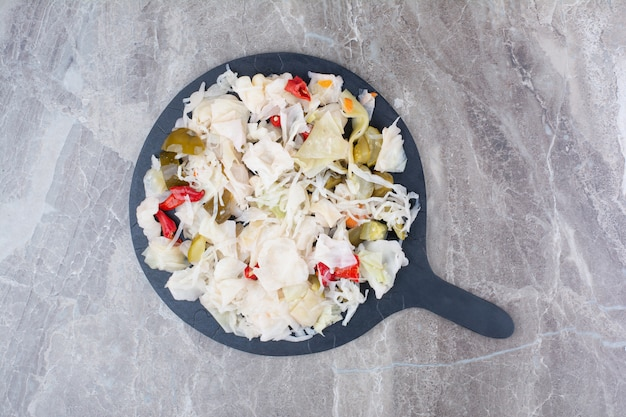 Marynowana kapusta z różnymi warzywami na ciemnym talerzu.