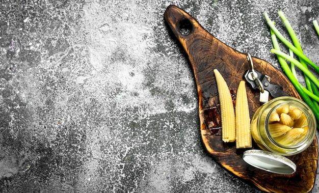 Marynowana kukurydza w szklanym słoiku. na rustykalnym tle.