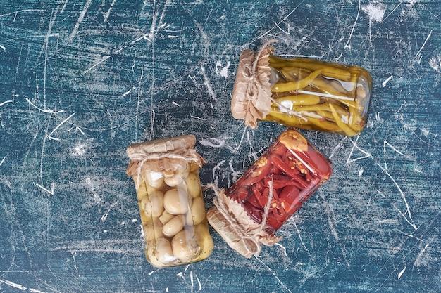 Marynowana papryka i grzyby w szklanym słoju na niebiesko.