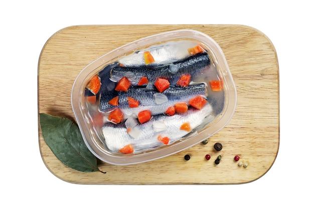Marynowana solona ryba w plastikowym słoiku na desce kuchennej, izolowana na białym tle