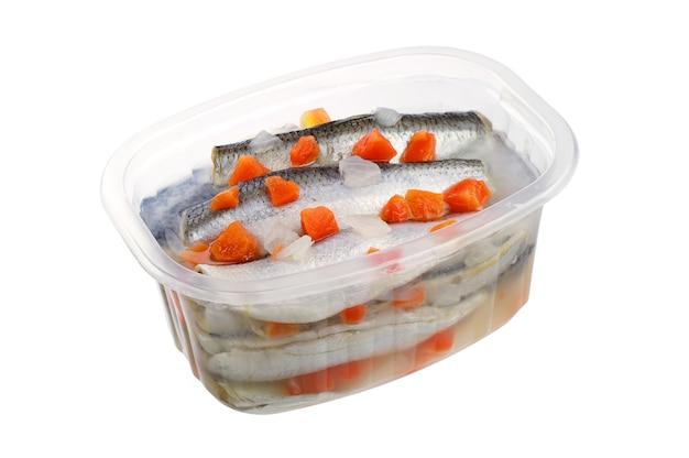 Marynowana solona ryba z marchewką w otwartym słoiku na białym tle