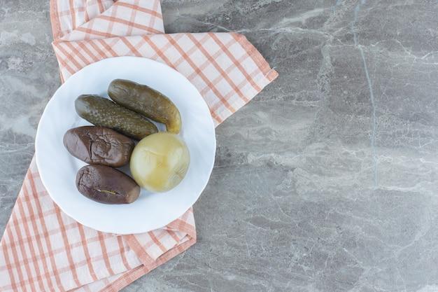 Marynowane bakłażany i pomidory na białym talerzu na szarym tle.