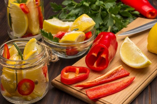 Marynowane cytryny z papryczką chili w słoikach, świeże cytryny i papryczka chili na desce do krojenia. produkty fermentujące. naturalny środek na przeziębienie.